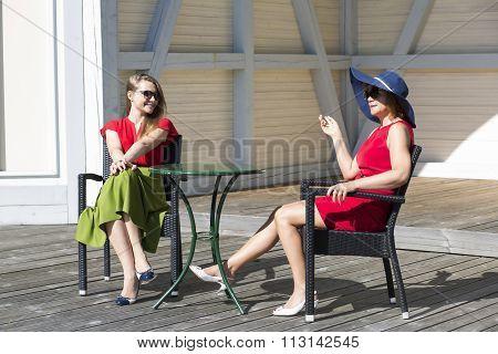 Small-talk between two aristocratic ladies in terrace