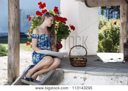 Graceful young lady draws in her album