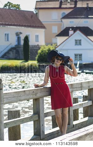 Attractive lady on the bridge holding hat