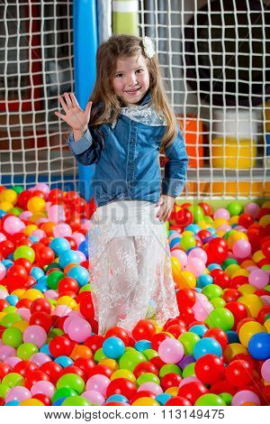 A girl in the playing room with many little colored balls