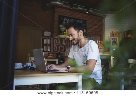 Happy male student writing text on net-book during breakfast in modern coffee shop