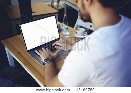 Cropped image of young man chatting via net-book during work break in coffee shop