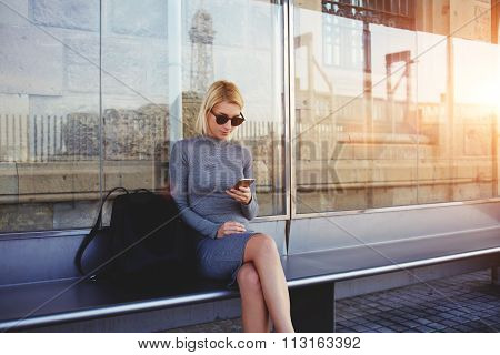 FFashionable woman tourist searching information about bus traffic using cell telephone