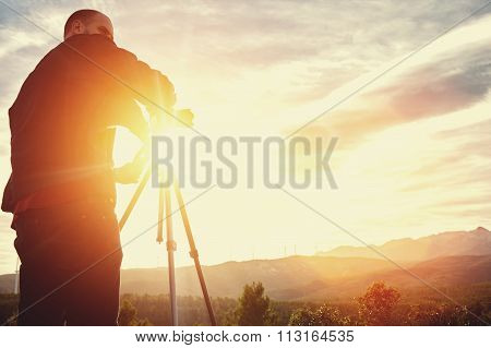 Male surveyor measures the distance while standing against sunset