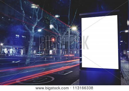 Public information board with cars lights on background, advertising mock up in urban setting