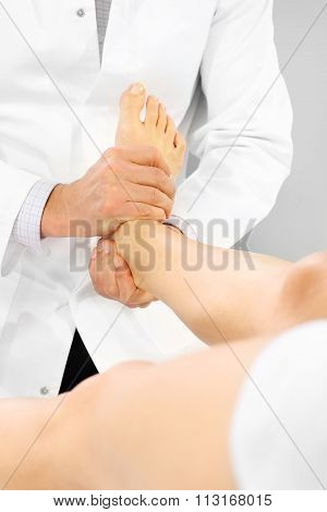 Orthopedic surgeon examines the patient's foot