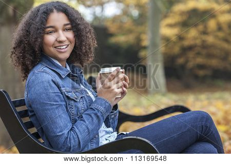 Beautiful happy mixed race African American girl teenager female young woman smiling and drinking takeaway coffee outside sitting on a park bench in autumn or fall