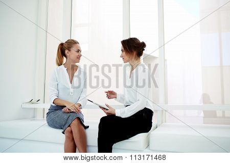 Two young successful female managing directors using digital tablet while discuss new business ideas