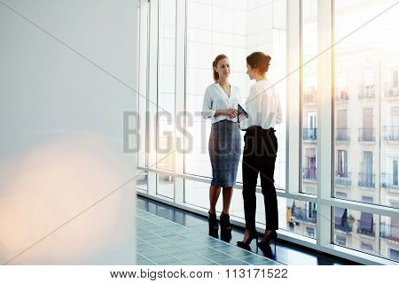 Businesswomen dressed in formal wear talking about work while meeting in hallway company
