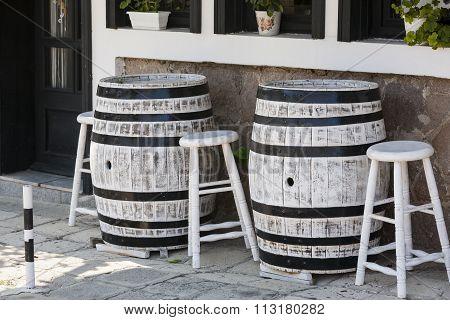The old oak wine barrel, metal rims with rust, barrel standing on the sidewalk.