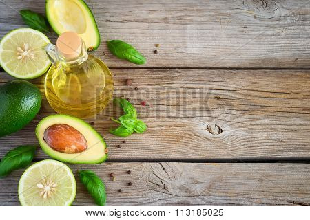 Food Background With Avocado, Lime, Olive Oil And Basil On Old W
