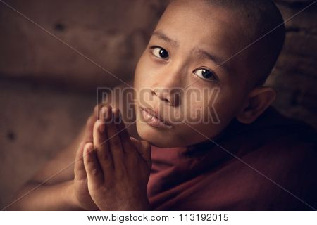 Portrait of young novice monk praying inside Buddhist temple, low light with noise setting, Bagan, Myanmar.
