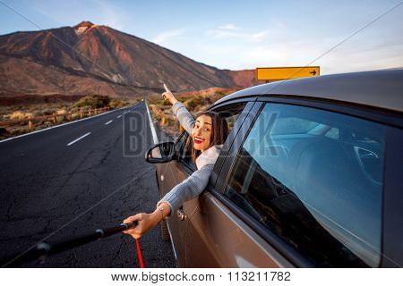 Woman in car with volcano on background