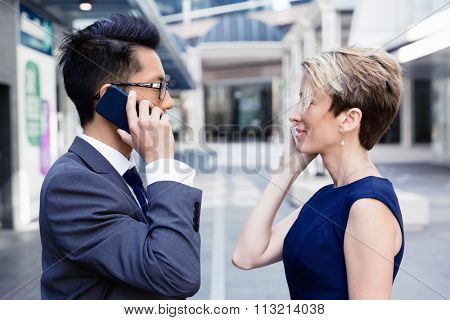 Business people standing in stret with their mobiles