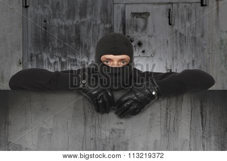 Ninja. Robber hiding behind a empty sign with space for text