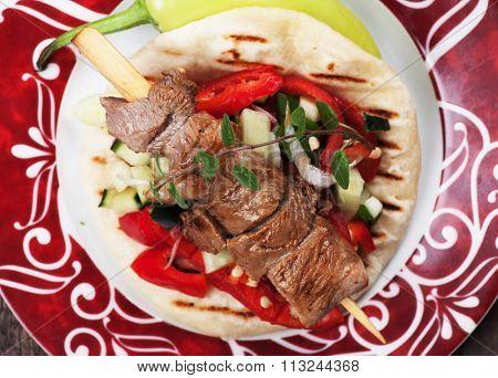 Souvlaki or kebab, grilled meat skewer served with pita bread