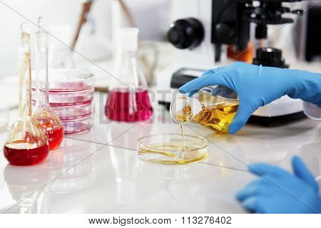 Science, Chemistry, Technology, Biology And People Concept - Young Female Scientist Mixing Reagents