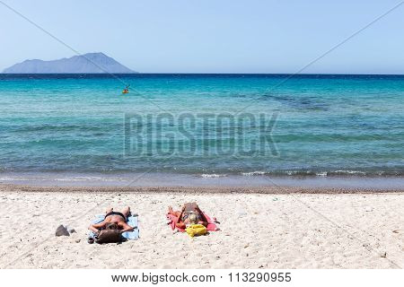 View Of Tourists Enjoy The Clear Water Of The Beautiful Beach In Milos Island, Cyclades, Greece
