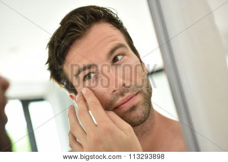 Handsome man applying facial cream in front of mirror