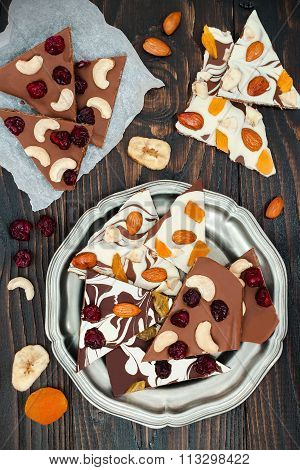 Holiday chocolate bark with dried fruits and nuts on a dark wood background. Top view. Dessert recip