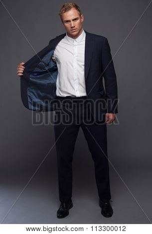 elegant young fashion man in tuxedo looking at the camera while holding his hands on his jacket and a leg behind the other. on gray background