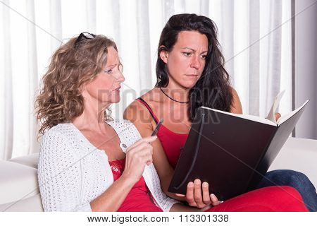 Two Attractive Woman Siiting On Couch Discussing And Taking Notes
