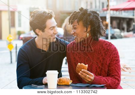 Romantic couple drinking coffee and eating croissants in a cafe. Young tourists enjoying breakfast in an outdoor cafe. Smiling couple in a happy conversation while eating brioches.