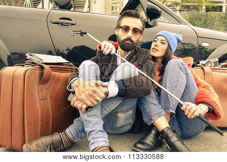 Hipster couple sitting on the street next their cabrio - Woman hugging her man with stick in hands -