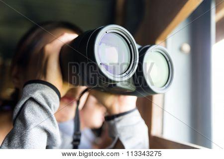 Asian Young woman use of the binocular for watching bird