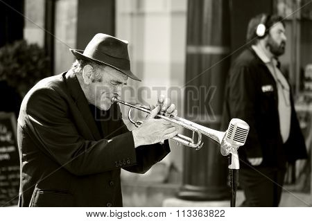 Man playing trumpet on street, ignored by man with headphones