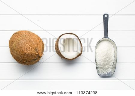 grated, whole and halved coconut on white table