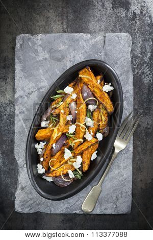 Spicy sweet potato fries with red onion, feta cheese and lemon.  Aerial view over slate.