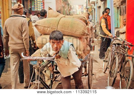 Hard Working Young Man Carries Heavy Bags Of Cargo On Vintage Bicycle
