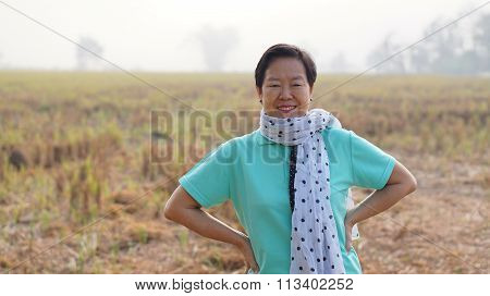 Happy Wealthy Asian Senior Woman Wearing Scraf In Front Of Her Farm Business