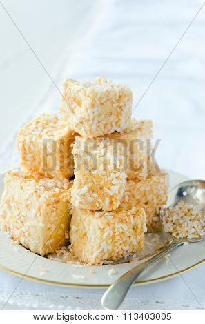 Cubes of marshmallow coated with roasted coconut bits, dessert treat bite size as a tea snack