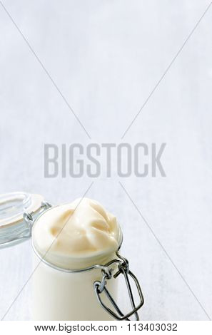 Bottle jar of homemade mayonaise on rustic white background with plenty of copy space