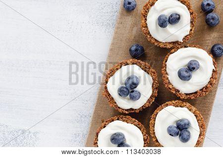 Blueberry tarts on a wooden platter, healthy dessert tart snack