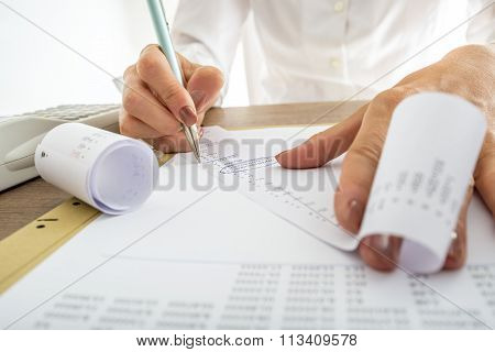Closeup Of Female Accountant Looking Through The Receipts