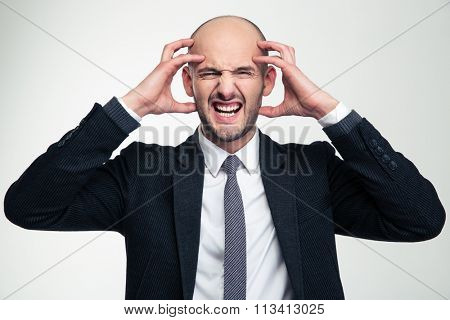 Portrait of annoyed depressed mad young business man in black suit isolated over white background