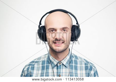 Cheerful handsome young man in checkered shirt listening to music in headphones over white background