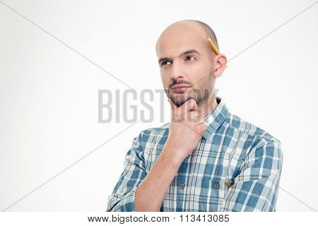 Portrait of concentrated thoughtful young man in checkered shirt with pencil behind ear isolated over white background