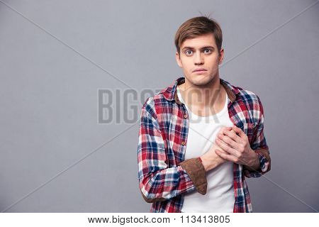 Stunned dazed young man in checkered shirt with hand on chest over grey background