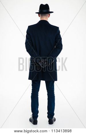 Back view of business man in black clothes and hat standing over white background
