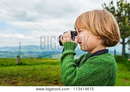 Cute little boy taking pictures with a camera