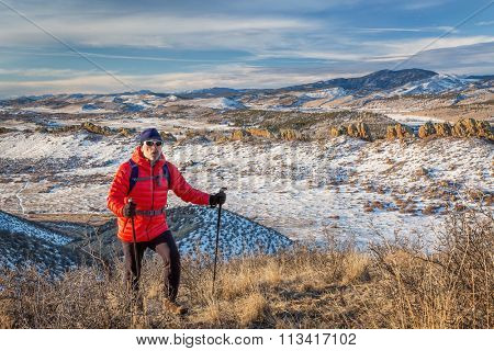 senior male hiker reaching top of a hill at foothills of Rocky Mountains - winter scenery at Devil's Backbone Open Space near Loveland, Colorado