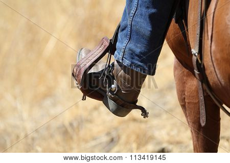 A cowboy boot in a saddle stirrup.