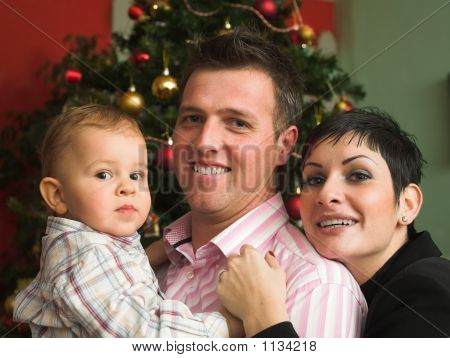 a family of three are very happy in front of a christmas tree. poster