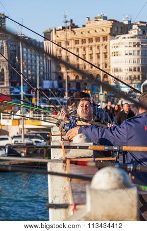 ISTANBUL, TURKEY - APRIL 10, 2015: unidentified anglers on the Galata bridge in Istanbul. Istanbul is the largest city in Turkey and a famous travel destination