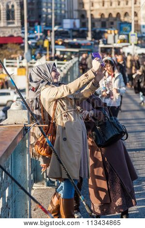 ISTANBUL, TURKEY - APRIL 10, 2015: unidentified islamic women making selfie photos on the Galata Bridge in Istanbul. Istanbul is the largest city in Turkey and a famous travel destination