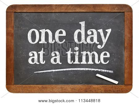 One day at a time  - white chalk text on a vintage slate blackboard
